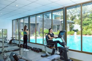 Gym room with a series of modern machines overlooking the pool nestled in green space.